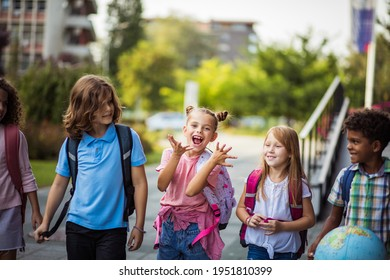 Group of elementary age schoolchildren outside. School kids going to school together.