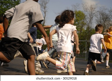 A group of elementary children racing across their school parking lot.