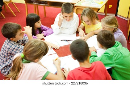 Group of elementary school children sitting around the table in the classroom and reading.  NOTE: All the drawings and artwork in the classroom are made by children.
