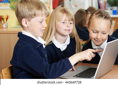 Group Of Elementary School Children Working Together In Computer Class
