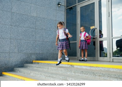 Group of elementary school girls running out of school buildings towards camera at the end of class