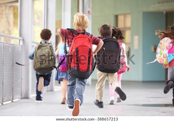 Ryhmä peruskoulun lapsia käynnissä koulussa, takakuva