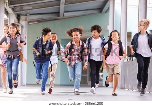 Grupo de crianças do ensino fundamental correndo em um corredor escolar