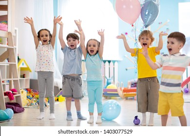 Group of emotional children friends with their hands raised. Kids have fun pastime in day care centre