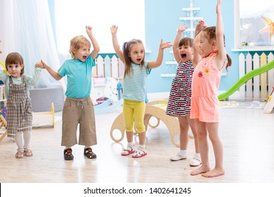 Group of emotional friends with their hands raised. Kids have fun pastime in day care centre