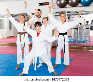 Group of emotional kids with man trainer posing in gym after taekwondo workout