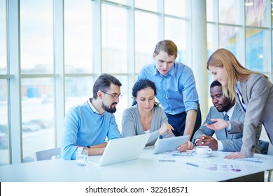 Group of employees consulting electronic data while making analysis