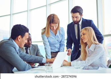 Group of employees discussing ideas and planning work in office