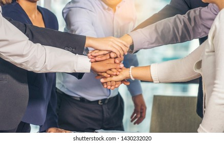 The group of employees hand in hand to show the best teamwork collaboration .Membership togetherness partnership and success Concept