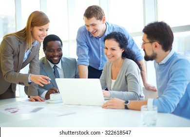 Group of employees with laptop networking at meeting in office