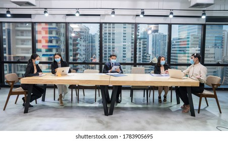 Group of employees were sitting in a meeting, working together  and wearing a mask to prevent Corona infection at office.New Normal and social distancing concept.