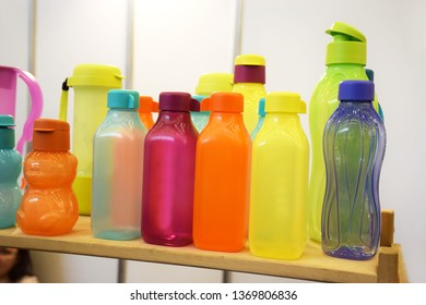 Group of empty sports water bottles of different colors and shapes on white background. Bright empty polyethylene bottles and tableware for fresh drinks.