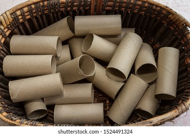 Group of empty tissue roll core put in the dark brown rattan wicker basket in the hotel toilet. Background for environmental and waste or global warming or recycle concept.