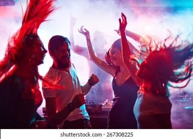 Group of energetic friends dancing in night club