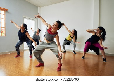 Group of energetic hip-hop dancers focused on training while gathered together in spacious dance hall - Shutterstock ID 702288490