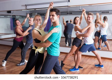 Group of energy people dancing salsa together in dance studio and smiling