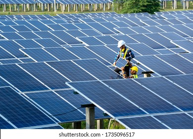 Group of engineer working on checking and maintenance with solar batteries near solar panels at sunny day in solar power plant station.