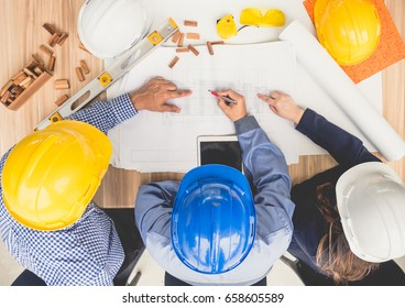Group of engineers and architects discussing on table with drawing/blueprint, wearing safety helmet working for industrial construction and engineering