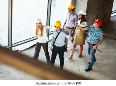 Group of engineers and experts discuss about construction site.Walking through building site,inspect and examining .