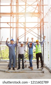 Group of engineers, man and woman, holding and catching hands together in construction site, standing  among the scaffold and pose greeting or cheerful action.