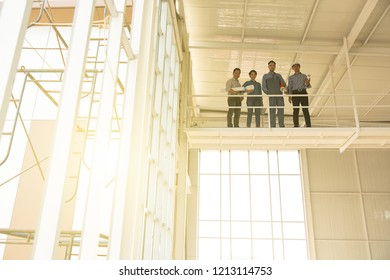 Group of engineers, man and woman, working together in construction site, standing on bridge among the scaffold.