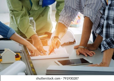 group of engineers, technician and architect planning about building plan with blueprint and construction tools on the conference table at construction site, business, industry, construction concept