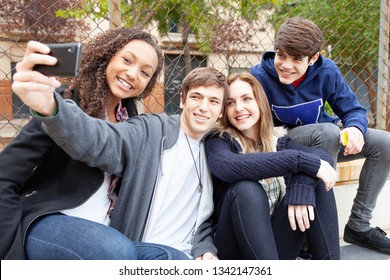 Group of ethnic diverse teenagers together in urban city using smartphone taking selfies photos with fun expressions, trendy friends outdoors. Adolescents networking technology, recreation lifestyle.