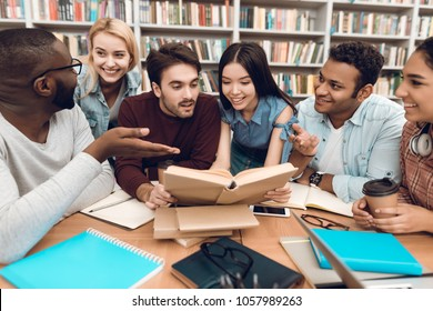 Group of ethnic multicultural students discussing studying sitting at table in library.
