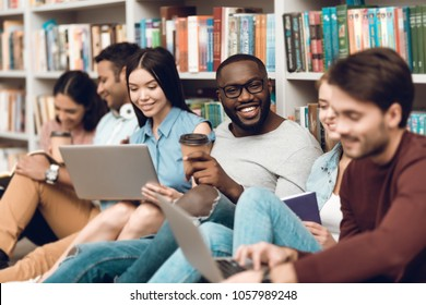 Group of ethnic multicultural students sitting, smiling and talking near bookshelf in library.