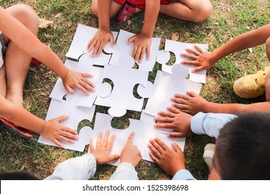 Group of ethnically diverse kids students is joined play jigsaw/puzzles pieces together in the playground. Teamwork, cooperation, learning, and education concept.