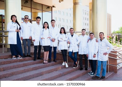 A group of European medical students presented outdoor against the university door on the steps.