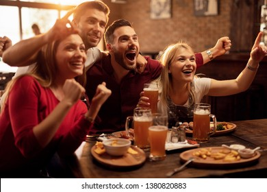 Group of excited fans having fun while watching sports match and cheering for their team in a pub.