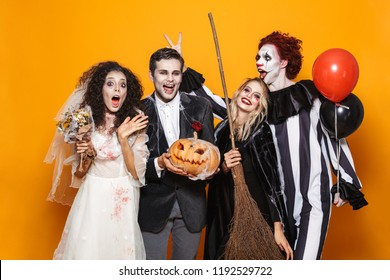 Group of excited friends dressed in scary costumes celebrating Halloween isolated over yellow background, holding balloons, curved pumpkin