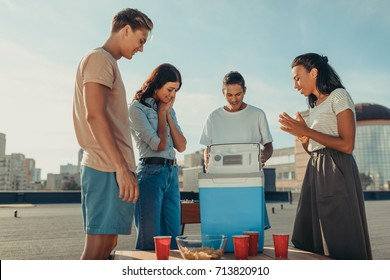 group of excited friends looking at portable fridge roof party