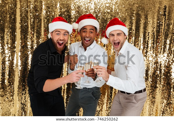 Group of excited handsome multiracial friends in christmas hats celebrating while standing and drinking champagne isolated over golden shiny background