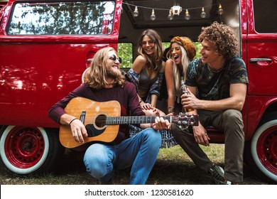 Group of excited hippies men and women having fun and playing guitar near vintage minivan into the nature