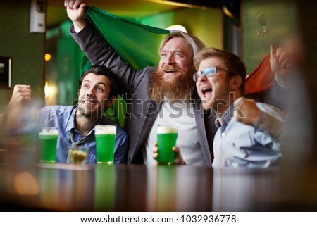 2675c9ae4 Group of excited men with beer and national irish flag watching football  match in pub