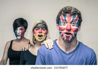 Group of excited people with painted flags on their faces shouting.