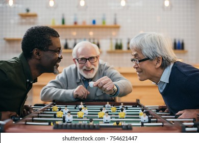 group of excited senior friends playing kicker at bar