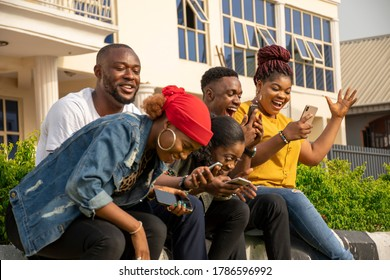 group of excited young black people using their phones