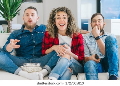 Group of excited young people, best friends spending day-off indoors, sitting on sofa in cozy living room watching soccer play live broadcast on tv cheering for favourite team.