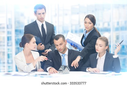 Group of executives debating while sitting at the table, blue background. Concept of teamwork and cooperation