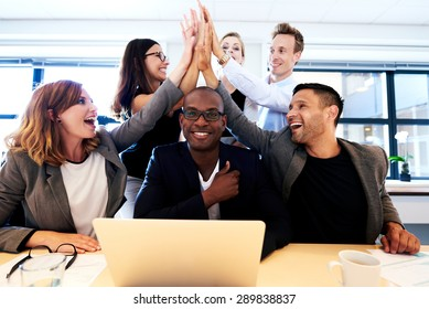 Group of executives smiling and group high fiving over black colleague's head