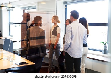 Group of executives standing in conference room gathered around white board