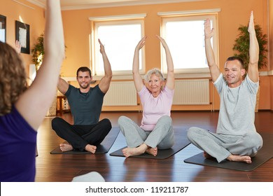 Group exercising cross-legged with fitness trainer in a health club