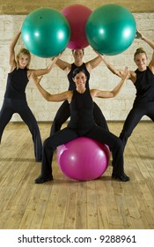 A group of the exercising women posing with big ball. They're smiling and looking at camera. Front view