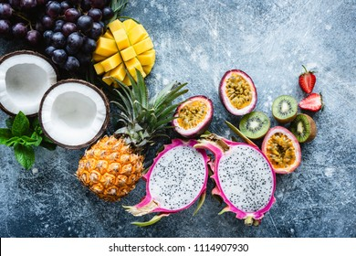 Group of exotic tropical fruits. Mango, dragon fruit, passion fruit, coconut, kiwi, pineapple and strawberry on concrete blue background. Fresh fruit flat lay