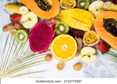 Group of exotic tropical fruits. Papaya, mango, dragon fruit, passion fruit, kiwi, strawberry, apple, banana, orange, longan, green leaves on white background Top view Flat lay