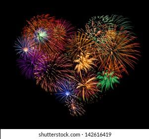 Group of exploding fireworks shaped like a heart.