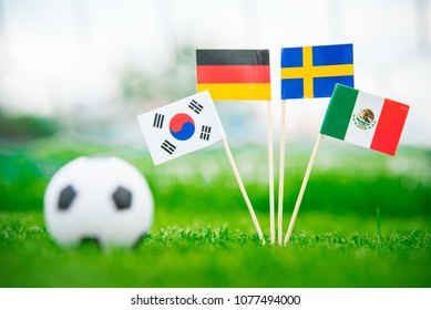Group F and football ball on green grass. National Flags of Germany, Mexico, Sweden, Korea Republic, South Korea